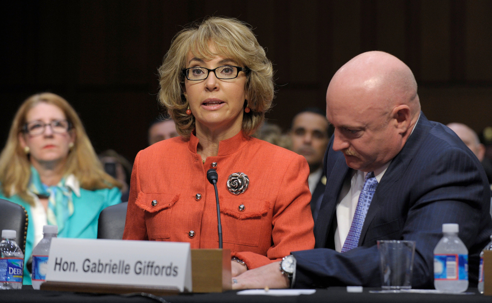. Former Arizona Rep. Gabrielle Giffords, who was seriously injured in the mass shooting that killed six people in Tucson, Ariz. two years ago, sits with her husband Mark Kelly, speaks on Capitol Hill in Washington, Wednesday, Jan. 30, 2013,  before the Senate Judiciary Committee hearing on gun violence.  (AP Photo/Susan Walsh)