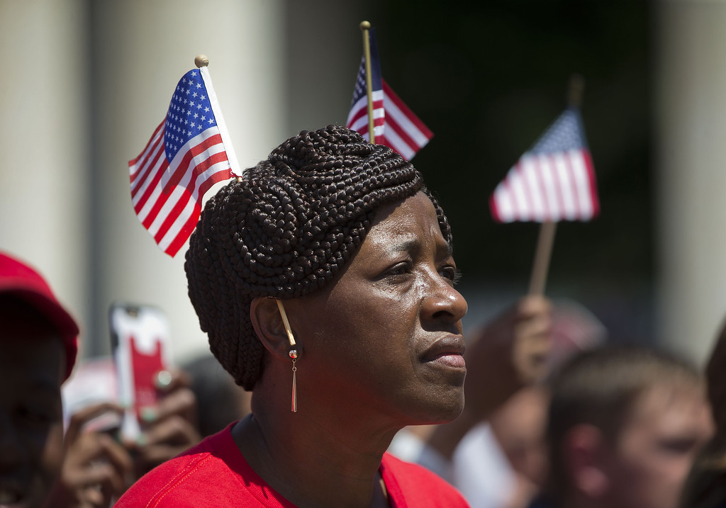. Sandra Bacchus of Coram, N.Y., listens as President Barack Obama speaks in the Memorial Amphitheater at Arlington National Cemetery in Arlington, Va., Monday, May 25, 2015, during a Memorial Day ceremony. (AP Photo/Pablo Martinez Monsivais)