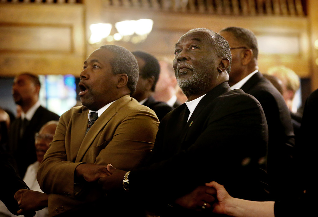 . From left, Reverend Richard Harkness holds hands with Reverend Jack Lewin during a prayer vigil held at Morris Brown AME Church for the victims of Wednesday\'s shooting at Emanuel AME Church on Thursday, June 18, 2015 in Charleston, S.C.  Dylann Storm Roof, 21, was arrested Thursday in the slayings of several people, including the pastor, at a prayer meeting inside the historic black church. (Grace Beahm/The Post And Courier via AP, Pool)