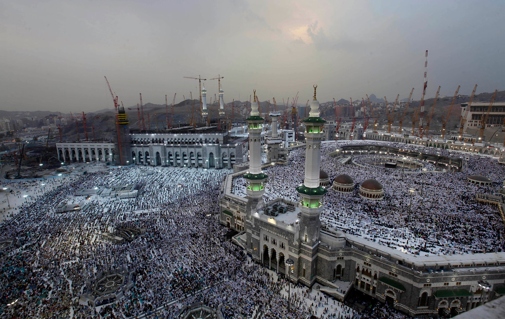 . Cranes rise at the site of an expansion to the Grand Mosque, right, as Muslims attend prayers at sunset at the mosque in the Muslim holy city of Mecca, Saudi Arabia, Thursday, Oct. 10, 2013. Every Muslim is required to perform the hajj, or pilgrimage, to Mecca at least once in his or her lifetime if able to do so. (AP Photo/Amr Nabil)