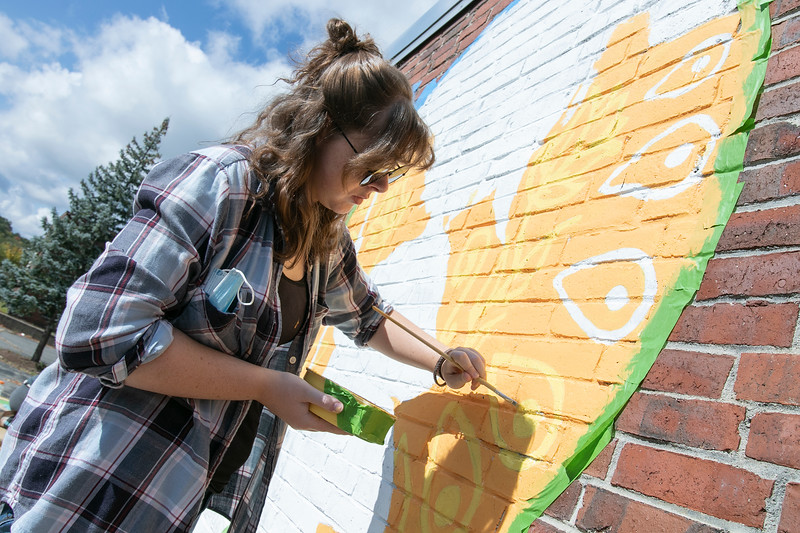 Artists Monique Guthrie and Erin Cregg, pictured, got a Community Development Block grant from the City of Fitchburg to paint a mural on the back wall of the Fitchburg Public Library. On Monday Guthrie was painting the Greek god Poseidon and Cregg, pictured, was painting the Greek god Athena. SENTINEL & ENTERPRISE/JOHN LOVE