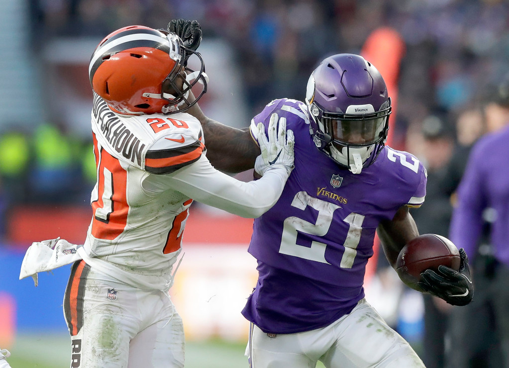 . Minnesota Vikings running back Jerick McKinnon (21) runs with the ball as Cleveland Browns safety Briean Boddy-Calhoun (20) defends during the second half of an NFL football game at Twickenham Stadium in London, Sunday Oct. 29, 2017. (AP Photo/Matt Dunham)