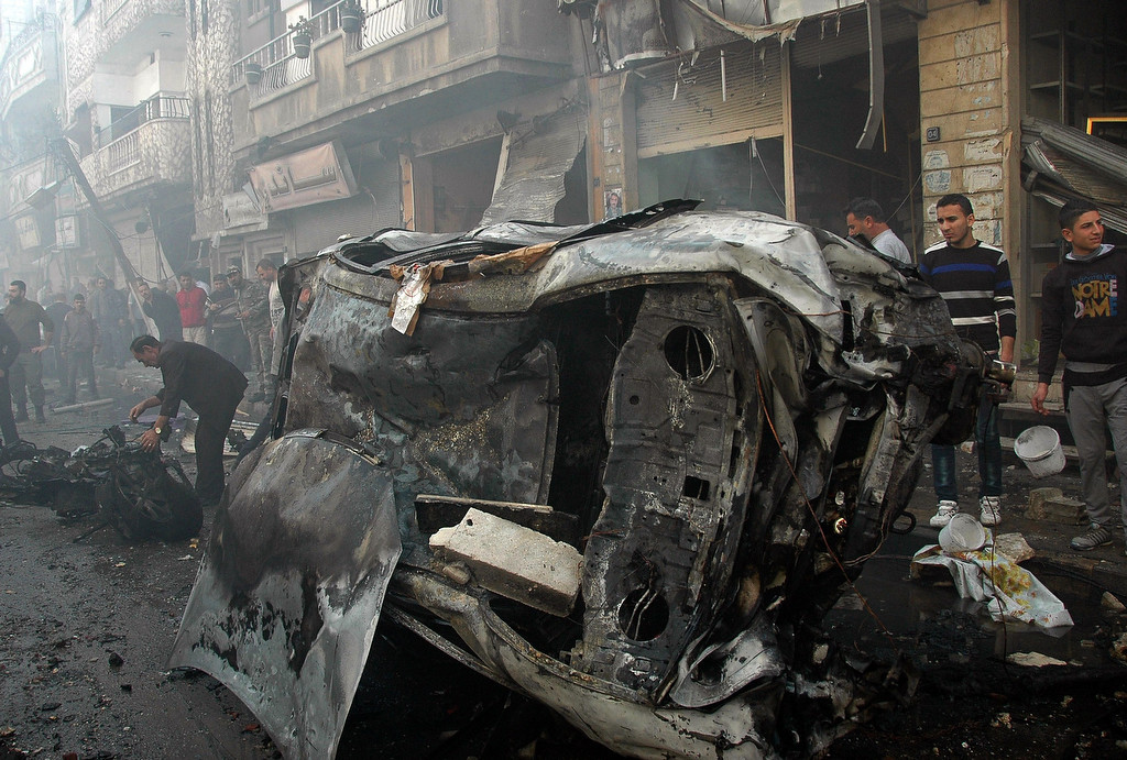 . A handout picture released by the official Syrian Arab News Agency (SANA) shows Syrians gathering near burnt-out vehicles following a car bomb explosion in al-Khudary Street in the Karm al-Loz neighbourhood of the central Syrian city of Homs on April 9, 2014. More than 150,000 people have been killed since the revolt began in March 2011 and nine million have been driven from their homes, including 2.6 million international refugees. (AFP PHOTO /HO/SANA)
