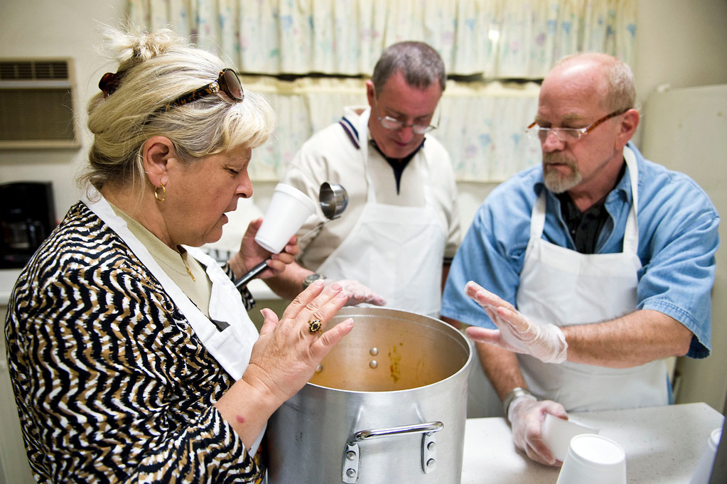 . From left, Nicolette Wingert, Phillip Stern and Christopher Barns say a prayer before distributing the soup at the Church of the Brethren kitchen in Glendora on Wednesday night, Nov. 27, 2013. Nicolette Wingert has been feeding the homeless six days a week for the past seven years with Nurses4Christ, a nonprofit organization she founded in 2006. (Photo by Watchara Phomicinda/San Gabriel Valley Tribune)