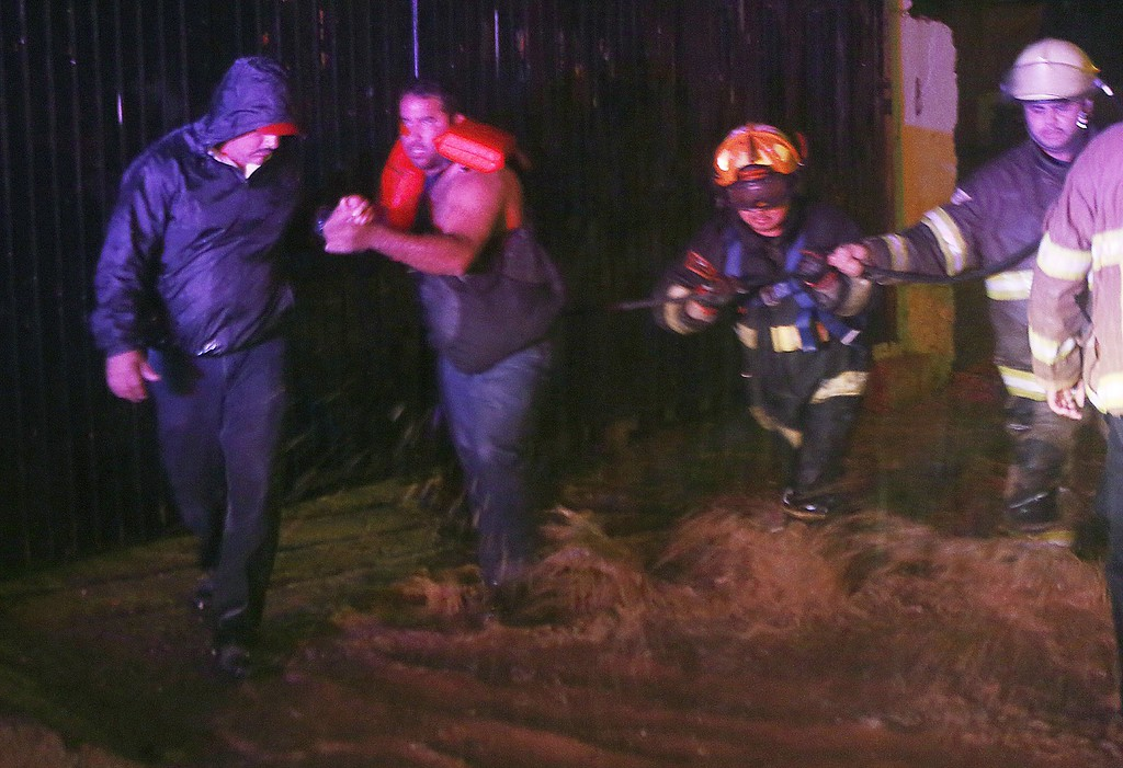 . Vicente Sanz, chief of the civil protection unit, left, takes the hand of a man who was rescued by Nogales firefighters when his vehicle stalled in a street with rushing water in Nogales, Sonora, Mexico, Wednesday, Sept. 17, 2014 in Nogales, Sonora, Mexico. Due to Hurricane Odile, the city received consistent rainfall on Wednesday afternoon and into the evening.  (AP Photo/Arizona Daily Star, Mamta Popat)