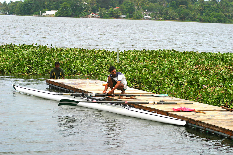 Shajjar holding the pair before they head out for a practice session.  The hyacinths are already creeping onto the dock again.  A Sri Lankan Navy guy is in the water trying to clear a path.  THe problem was that every time the wind changed direction, the plants would be all over the course again because they are not anchored but float.
