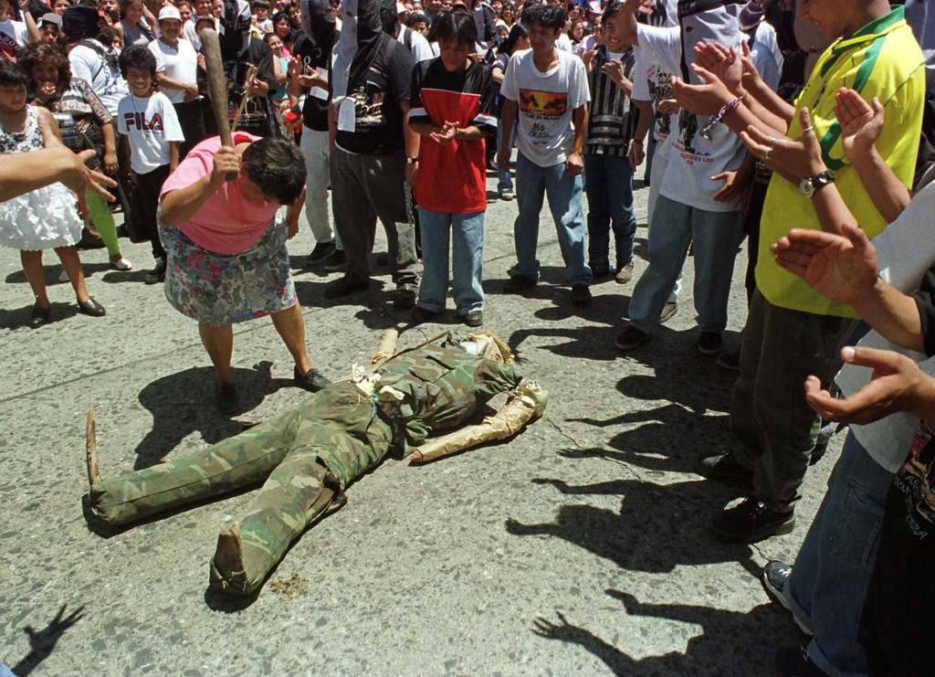 """. An unidentified woman beats an effigy of former military leader Efrain Rios Montt during the 101st annual Huelga de Dolores in Guatemala City Friday, March 26, 1999. The annual march is a method in which the university students let their grievances with the Guatemalan government be known. Rios Montt was a general who seized power in a March 1982 coup and governed until he was overthrown in August 1983.  During his rule, the army burned Indian villages and killed thousands of suspected leftists.  While beating the effigy, other students shouted, \""""First Pinochet, now Rios Montt,\"""" in a cry for the former military leader to be tried for his crimes. (AP Photo/Scott Dalton)"""