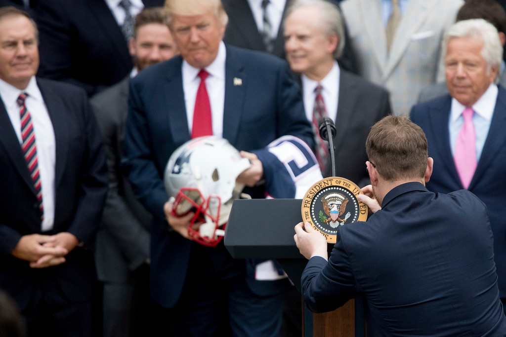 . An aide removes the presidential seal from a podium after President Donald Trump was presented a New England Patriots football helmet and jersey by New England Patriots head coach Bill Belichick, left, and New England Patriots owner Robert Kraft, right, during a ceremony on the South Lawn of the White House in Washington, Wednesday, April 19, 2017, where the president honored the Super Bowl Champion New England Patriots for their Super Bowl LI victory. (AP Photo/Andrew Harnik)