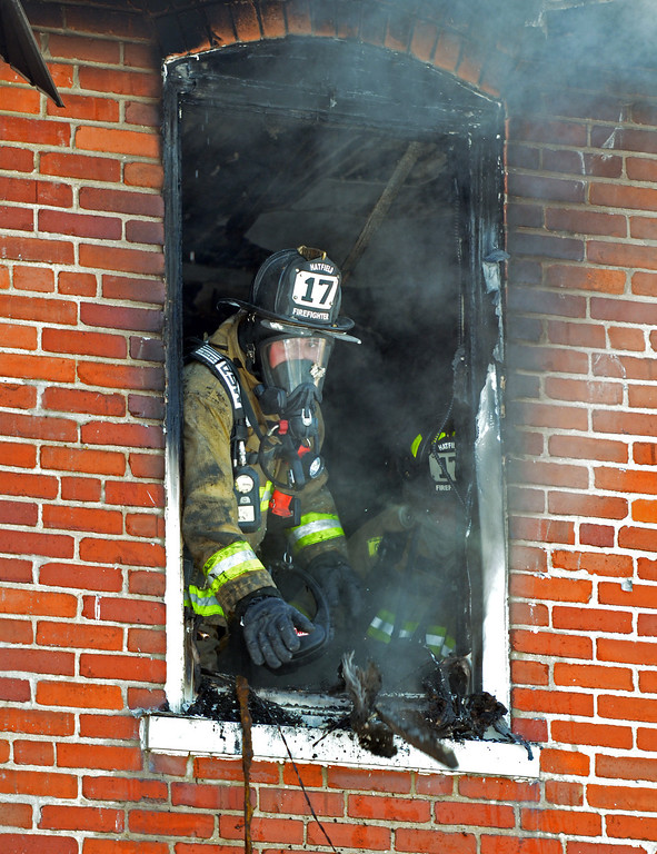 . A firefighter removes debris from second floor of home  on Forty Foot Road in Hatfield Township following a fire.   Thursday, January 23, 2014.  Photo by Geoff Patton