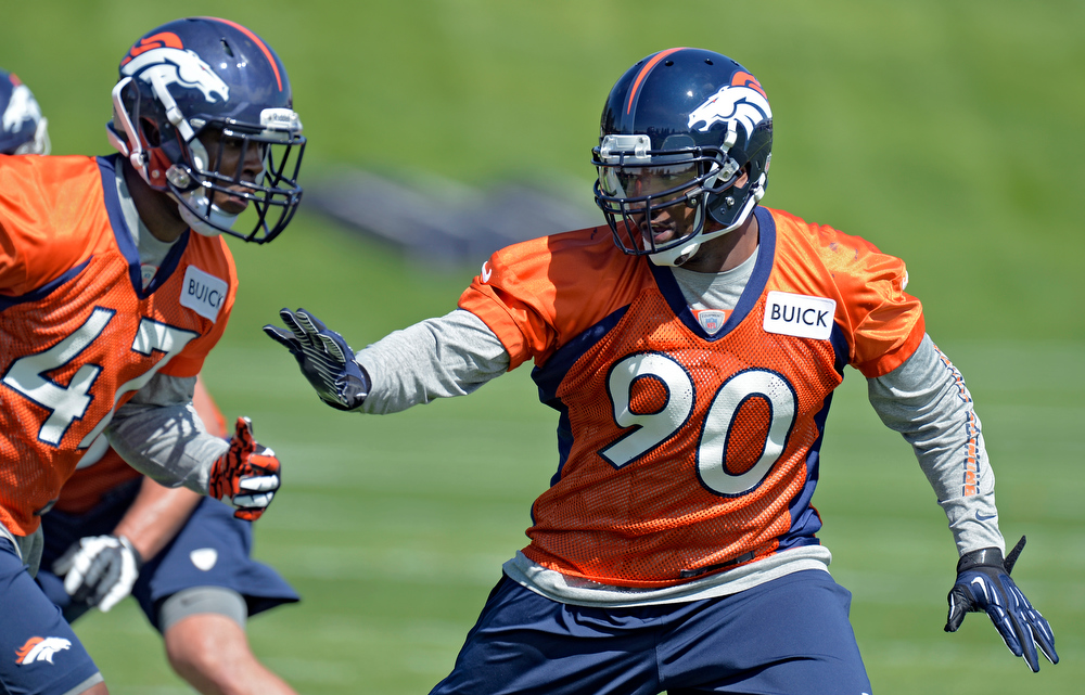 . Shaun Phillips (90) of the Denver Broncos runs through drills with Lerentee McCray (47) during the teams OTAs May 20, 2013 at Dove Valley. All offseason training activities (OTAs) are voluntary until the mandatory minicamp June 11-13. (Photo By John Leyba/The Denver Post)