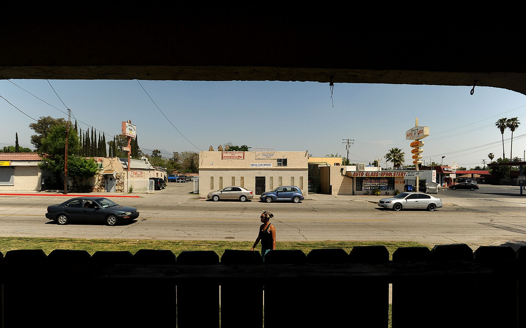 . A woman walks along the 1200 block of North Sierra Way towards in San Bernardino April 22, 2013.   GABRIEL LUIS ACOSTA/STAFF PHOTOGRAPHER.