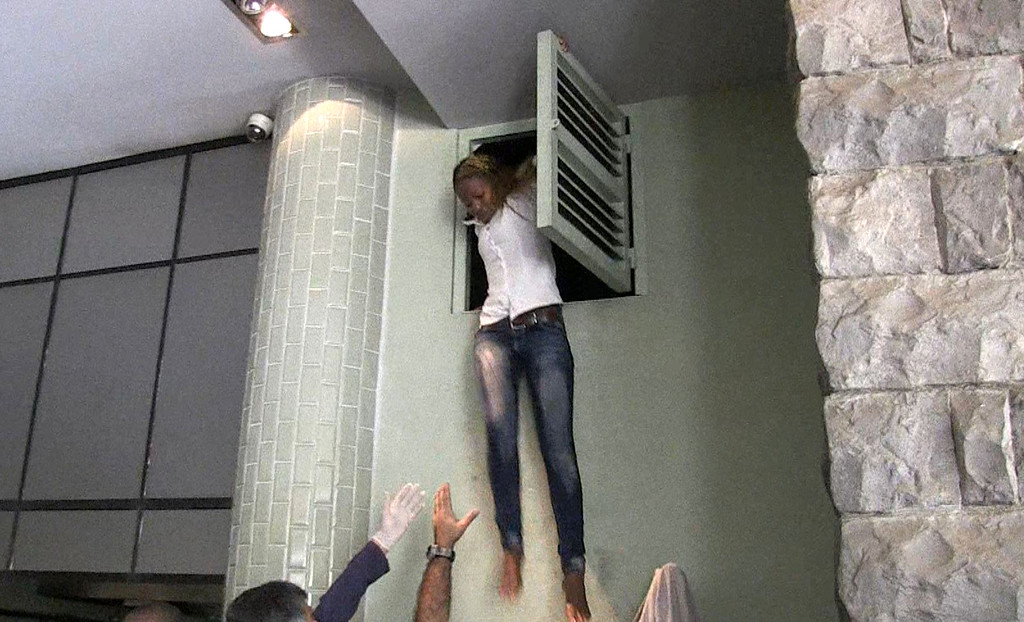 . An image grab taken from AFP TV shows a Kenyan woman coming out of an air vent where she was hiding during an attack by masked gunmen at a shopping mall in Nairobi on September 21, 2013.  AFP PHOTO/AFPTV/NICHOLE Sobecki/AFP/Getty Images