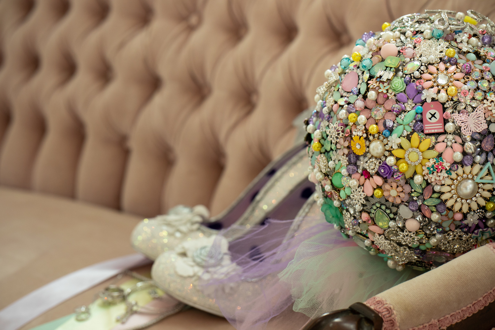 a wedding bouquet made out of costume jewelry sitting on an antique couch