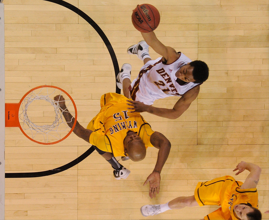 . Denver Pioneers guard Bryant Rucker (21) goes up for a shot on Wyoming Cowboys guard Jerron Granberry (15) during the first half December 15, 2013 Magness Arena. (Photo by John Leyba/The Denver Post)