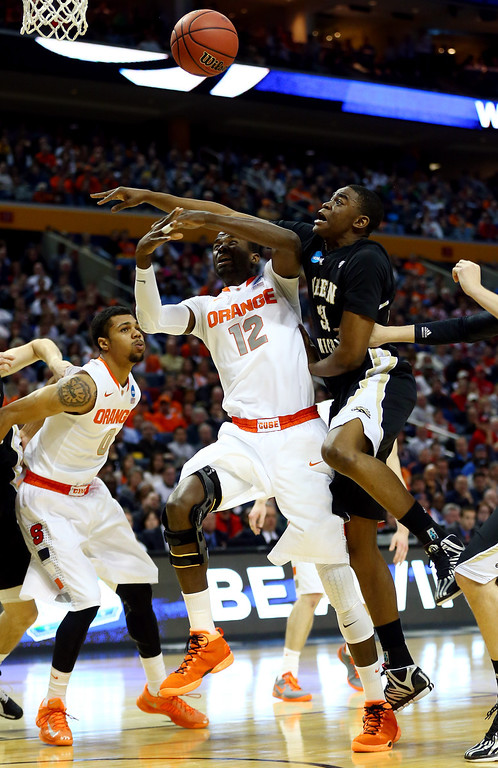 . BUFFALO, NY - MARCH 20:  Baye-Moussa Keita #12 of the Syracuse Orange goes to the basket as A.J. Avery #34 of the Western Michigan Broncos defends during the second round of the 2014 NCAA Men\'s Basketball Tournament at the First Niagara Center on March 20, 2014 in Buffalo, New York.  (Photo by Elsa/Getty Images)