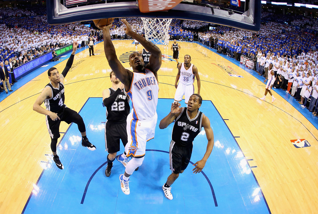 . OKLAHOMA CITY, OK - MAY 27: Serge Ibaka #9 of the Oklahoma City Thunder drives to the basket against Kawhi Leonard #2 of the San Antonio Spurs in the first half during Game Four of the Western Conference Finals of the 2014 NBA Playoffs at Chesapeake Energy Arena on May 27, 2014 in Oklahoma City, Oklahoma. (Photo by Ronald Martinez/Getty Images)