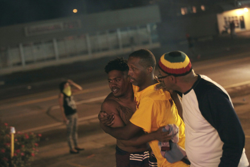 . A man suffering the effects of tear gas is helped at a protest of the death of Michael Brown August 17, 2014 in Ferguson, Missouri. Tensions still run high in the Ferguson community after 18 -year-old Michael Brown was killed by a Ferguson police officer August 9 on Canfield Drive.  (Photo by Joshua Lott/Getty Images)