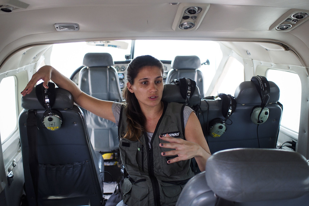 """. Greenpeace spokeswoman and wood campaigner Marina Lacorte, speaks before departing to overfly areas of illegal exploitation of timber, as part of the second stage of the \""""The Amazon\'s Silent Crisis\"""" report in Santarem, state of Para, Brazil, on October 14, 2014. RAPHAEL ALVES/AFP/Getty Images"""