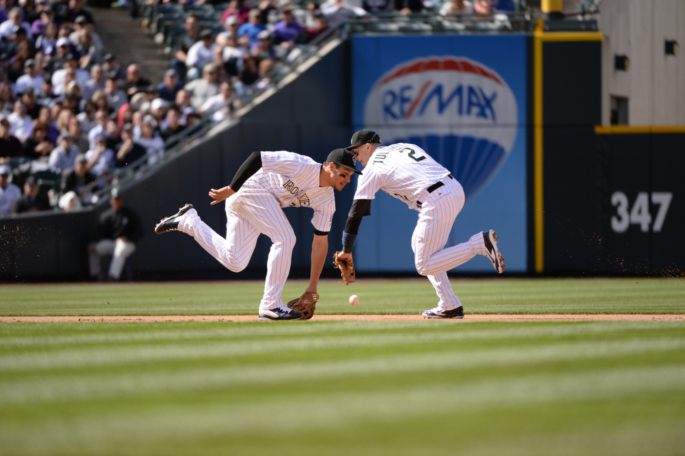 . The Rockies\' Nolan Arenado (28) and Troy Tulowitzki (2) rush to field a ball hit by the Diamondbacks\' Martin Prado during the fourth inning. The Colorado Rockies hosted the Arizona Diamondbacks in the Rockies season home opener at Coors Field in Denver, Colorado Friday, April 4, 2014. (Photo by Hyoung Chang/The Denver Post)