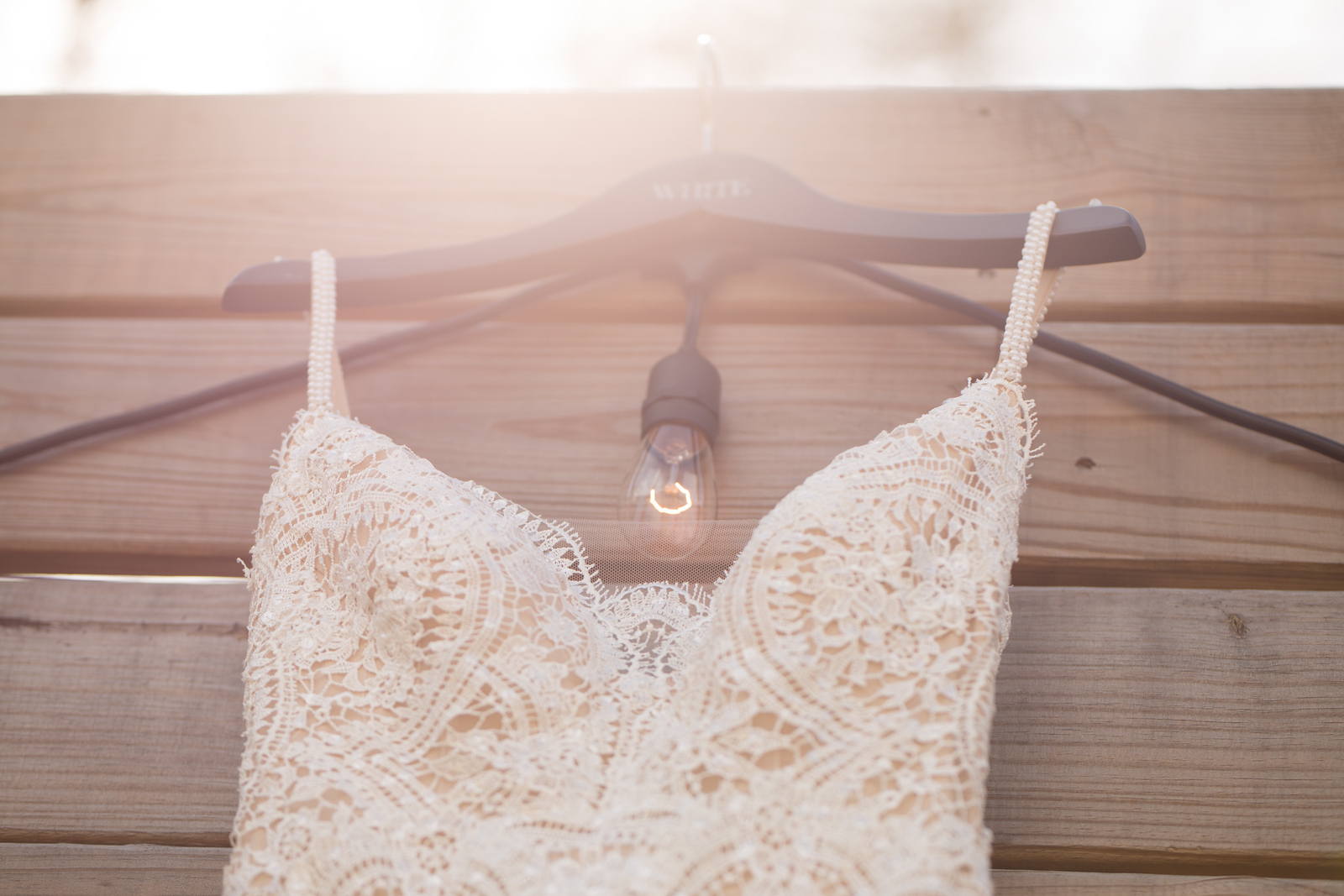 white lace wedding dress on a hanger with a lightbulb with sunlight glare