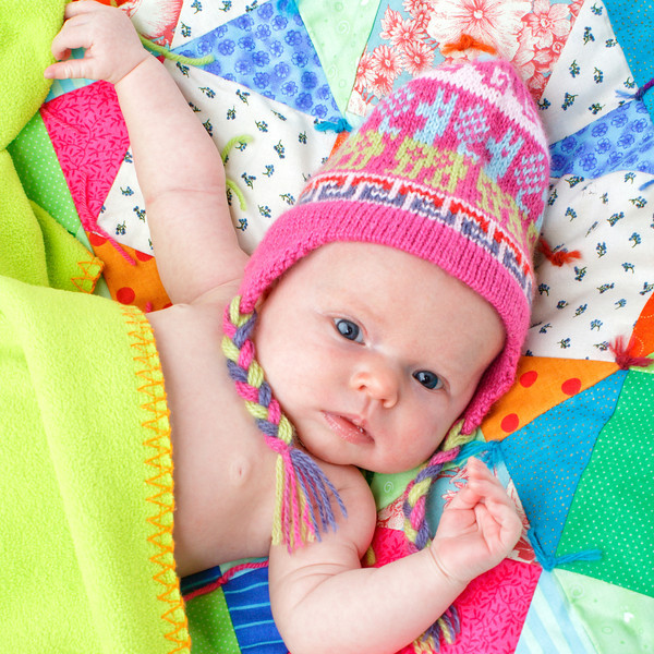 Baby with colorful knit hat and patchwork quilt