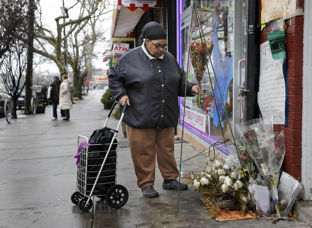 . A woman, who did not want to give her name, places flowers at a memorial for Eric Garner near the site of his death in the borough of Staten Island Wednesday, Dec. 3, 2014., in  New York. A grand jury is deciding whether to indict a New York City police officer in the chokehold death of Garner. (AP Photo/Seth Wenig)