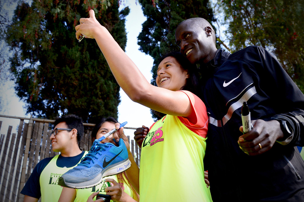 . Joselin Rivas, 17, of Foshey Learning Center, takes a selfie with elite marathon runner Lani Rutto, of Kenya, as he signs shoes and jerseys for students of Students Run LA program Friday, March 7, 2014 in Griffith Park. Elite marathon runners were training at the park for Sunday\'s LA Marathon before visiting with the students, who also will be running in Sunday\'s marathon. (Photo by Sarah Reingewirtz/Pasadena Star-News)