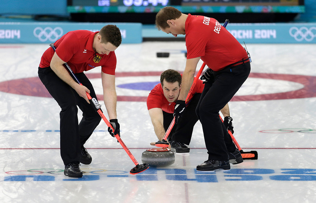 . Germany\'s skip Felix Schulze, center, delivers the rock while Christopher Bartsch, left, and Sven Goldemann, right, sweep the ice during the men\'s curling match against Denmark at the 2014 Winter Olympics, Sunday, Feb. 16, 2014, in Sochi, Russia. (AP Photo/Wong Maye-E)