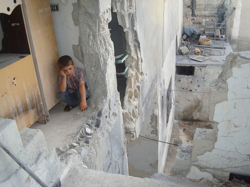 . A boy sits at his parents\' house, damaged by shelling by forces loyal to Syria\'s President Bashar al-Assad, in Talbiseh, near Homs August 31, 2012.   REUTERS/Shaam News Network/Handout