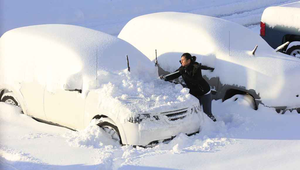 . Christine Bloom works to clear snow off her vehicle to try and make it to work in Hamburg, N.Y.,  on Wednesday, Nov. 19, 2014.  A ferocious storm dumped massive piles of snow on parts of upstate New York, trapping residents in their homes and stranding motorists on roadways, as temperatures in all 50 states fell to freezing or below.  (AP Photo/The Buffalo News, Harry Scull Jr.)