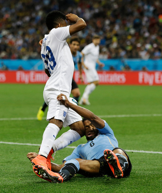 . England\'s Raheem Sterling runs into Uruguay\'s Alvaro Pereira with his knee during the group D World Cup soccer match between Uruguay and England at the Itaquerao Stadium in Sao Paulo, Brazil, Thursday, June 19, 2014. Pereira was knocked out by the blow.  (AP Photo/Kirsty Wigglesworth)