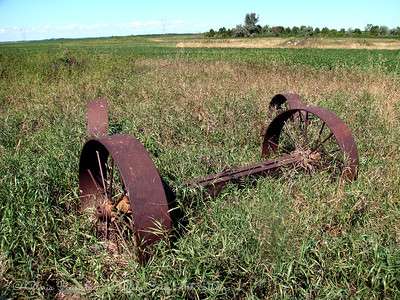 Rusted old John Deer Axles in the grass field