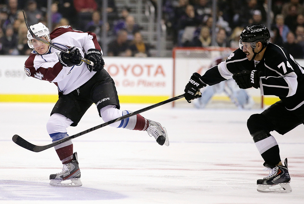 . Colorado Avalanche\'s Tyson Barrie, left, passes the puck against Los Angeles Kings\' Dwight King during the first period of an NHL hockey game on Saturday, Nov. 23, 2013, in Los Angeles. (AP Photo/Jae C. Hong)