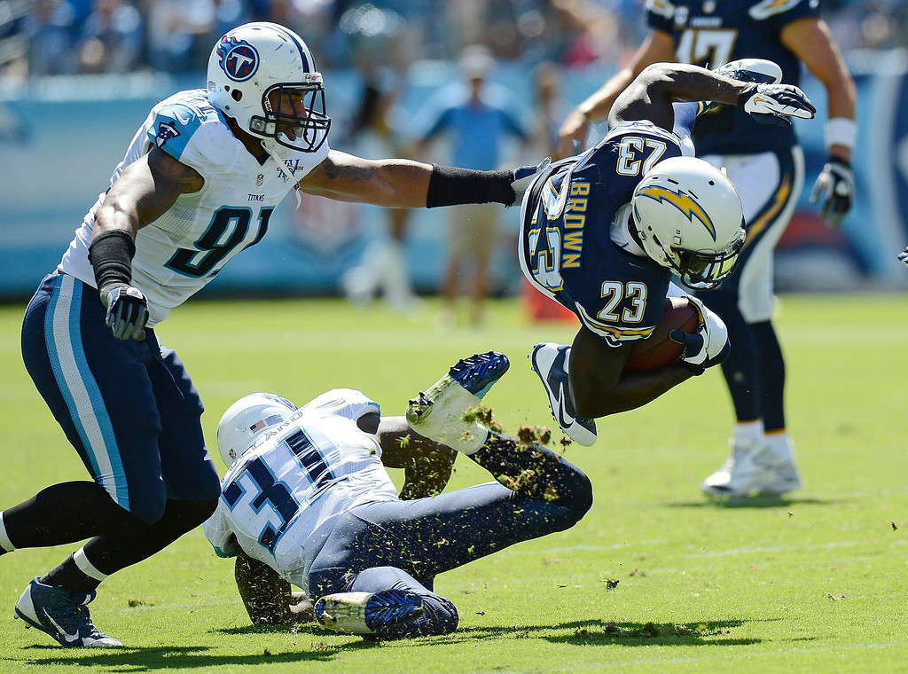 . San Diego Chargers running back Ronnie Brown (23) is brought down by Tennessee Titans defenders Bernard Pollard (31) and Derrick Morgan (91) in the second quarter of an NFL football game on Sunday, Sept. 22, 2013, in Nashville, Tenn. (AP Photo/Mark Zaleski)
