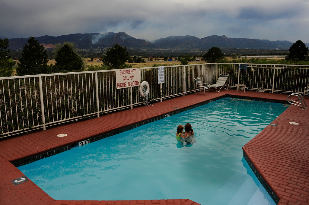 . Evacuees Alexandrea Hermes and her daughter, Ava, 5, watch as smoke rises in mountains behind them, Thursday June 28, 2012, while swimming in the pool at the hotel where they are now staying. Alexandrea\'s husband is active duty and the family lives on base at the Air Force Academy. They were forced to evacuate their home that is in the path of the Waldo Canyon fire in Colorado Springs. RJ Sangosti, The Denver Post