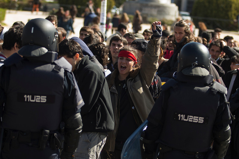 . A student shouts slogans as riot police stand guard during the first day of a student strike to protest a government education reform and cutbacks in grants and staffing, at Complutense University in Madrid, Spain, Wednesday, March 26, 2014. Spanish police say they have arrested more than 50 students when the police moved in to end the occupation of a campus building after the university had asked them to intervene. Students, many with their faces covered, set fire to trash containers and set up barricades on at least two streets in the university complex during the protest. (AP Photo/Andres Kudacki)