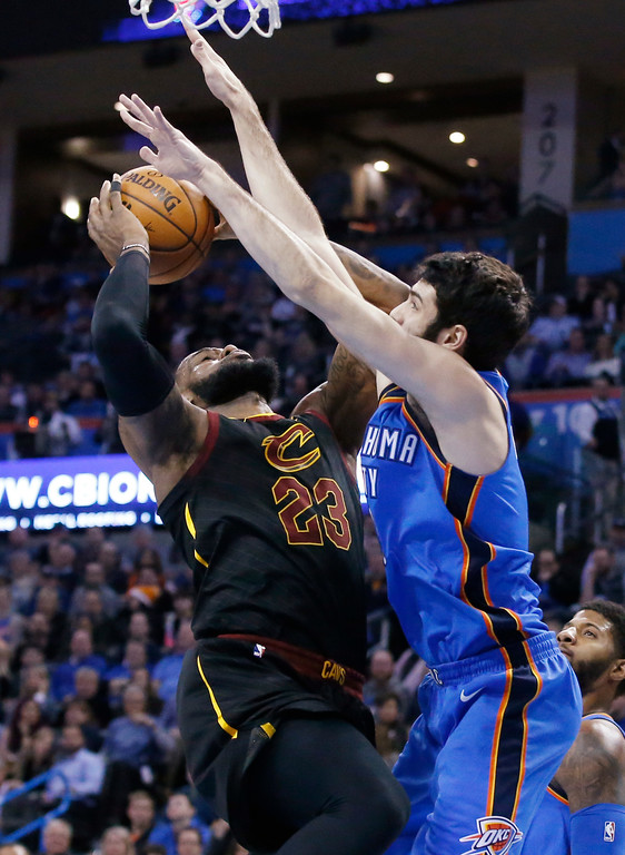 . Cleveland Cavaliers forward LeBron James, left, is fouled by Oklahoma City Thunder guard Alex Abrines as he shoots during the first half of an NBA basketball game in Oklahoma City, Tuesday, Feb. 13, 2018. (AP Photo/Sue Ogrocki)