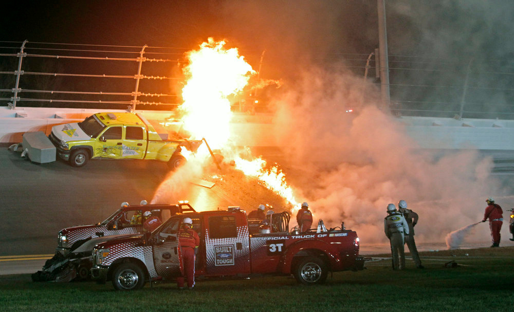 Description of . Emergency workers try to put out a fire after Juan Pablo Montoya's car struck the truck during the NASCAR Daytona 500 auto race at Daytona International Speedway in Daytona Beach, Fla., Monday, Feb. 27, 2012. (AP Photo/Bill Friel)