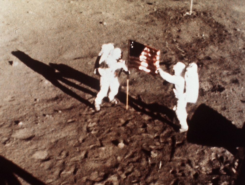 ". Apollo 11 astronauts Neil Armstrong and Edwin E. ""Buzz\"" Aldrin, the first men to land on the moon, plant the U.S. flag on the lunar surface, July 20, 1969.  Photo was made by a 16mm movie camera inside the lunar module, shooting at one frame per second.  (AP Photo/NASA)"