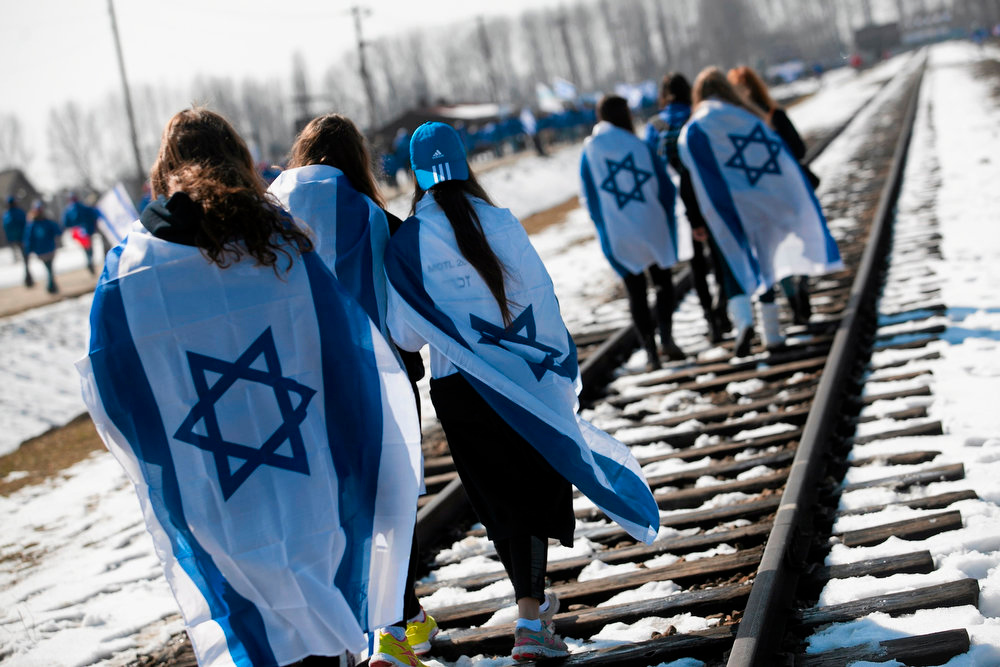 "Description of . People wear Israeli flags around their shoulders as they walk on the railroad tracks inside the former Nazi death camp of Birkenau (Auschwitz II) in Oswiecim-Brzezinka, southern Poland on April 8, 2013. Thousands of mainly Jewish people participated in the 22nd annual ""March of the Living\"", a Holocaust commemoration. REUTERS/Jakub Ociepa/Agencja Gazeta"