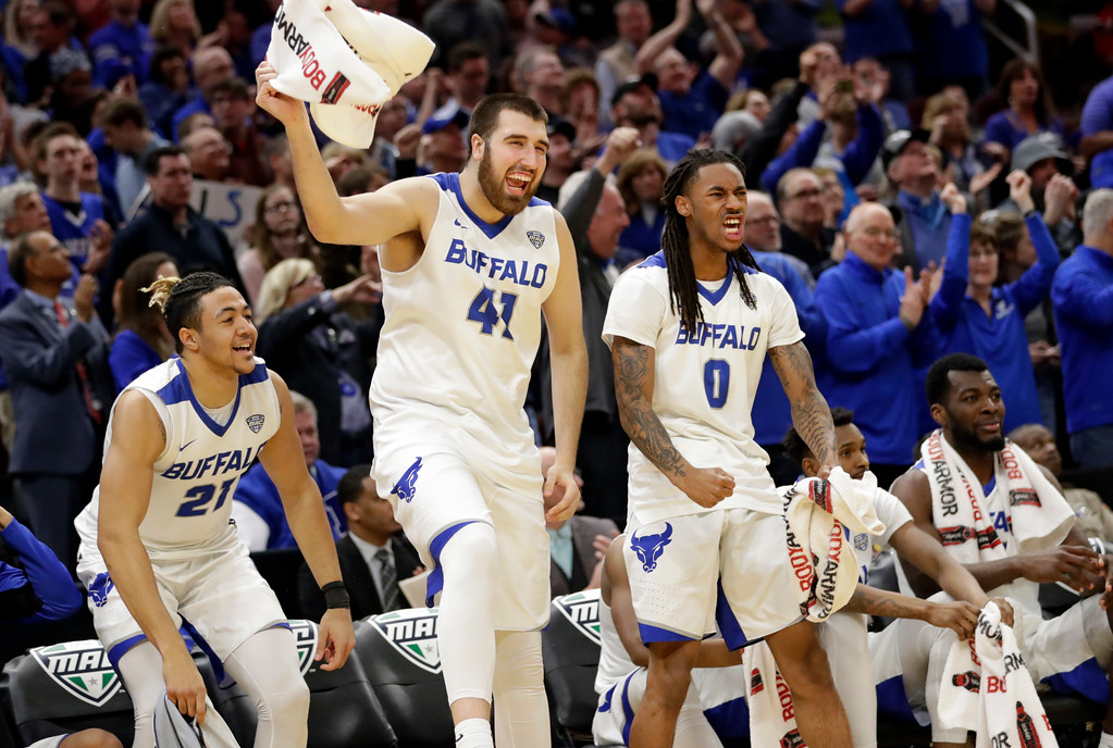 . Buffalo Bulls\' Dominic Johnson (21), Buffalo\'s Brock Bertram (41), and Buffalo\'s James Reese (0) cheer during the second half of an NCAA college basketball championship game against Toledo in the Mid-American Conference tournament, Saturday, March 10, 2018, in Cleveland. Buffalo won 76-66. (AP Photo/Tony Dejak)