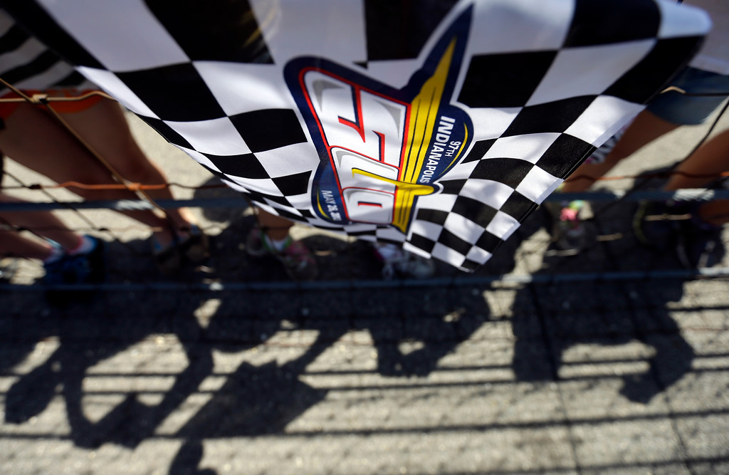 . An Indianapolis 500 flag hangs near a group of school children hoping for a driver\'s autographs during practice for the Indianapolis 500 auto race at the Indianapolis Motor Speedway in Indianapolis, Wednesday, May 15, 2013. (AP Photo/Darron Cummings)