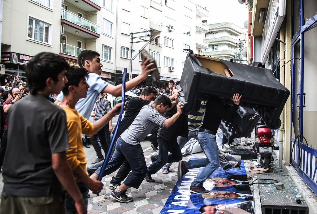 """. People attack the Soma offices of Prime Minister Recep Tayyip Erdogan\'s Justice and Development Party during his visit to the coal mine in Soma, Turkey, Wednesday, May 14, 2014. A violent protest erupted Wednesday in the Turkish city of Soma, where at least 238 coal miners have died after a mine explosion. Many in the crowd expressed anger at Prime Minister Recep Tayyip Erdogan\'s government. Rocks were being thrown and some people were shouting that Erdogan was a \""""Murderer!\"""" and a \""""Thief!\"""" (AP Photo/Emrah Gurel)"""