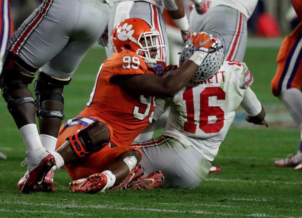 . Clemson defensive end Clelin Ferrell (99) grabs Ohio State quarterback J.T. Barrett (16) after the throw during the second half of the Fiesta Bowl NCAA college football game, Saturday, Dec. 31, 2016, in Glendale, Ariz. (AP Photo/Rick Scuteri)