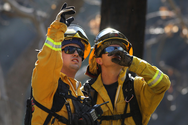 . A Cal Fire crew work at a flare-up at the Colby Fire burning for a second day in the hillside above Highway 39 on January 17, 2014 in Azusa, California. The so-called Colby Fire, has burned about 1,700 acres in the Angeles National Forest north of Glendora and Azusa. (Photo by Jonathan Alcorn/Getty Images)