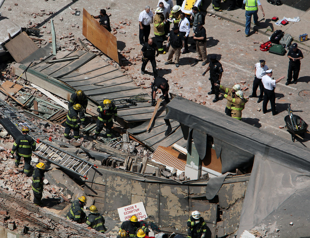 . Rescue personnel search the scene of a building collapse on the edge of downtown Philadelphia Wednesday June 5, 2013. (AP Photo/Jacqueline Larma)