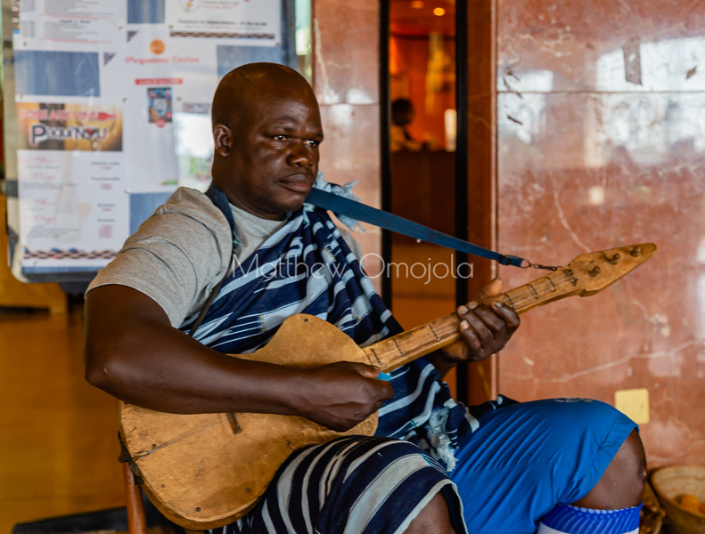 Promoting culture. Ivorian African man in ivorian African attire playing musical instrument in President Hotel Yamoussoukro Cote d'Ivoire. Ivory Coast