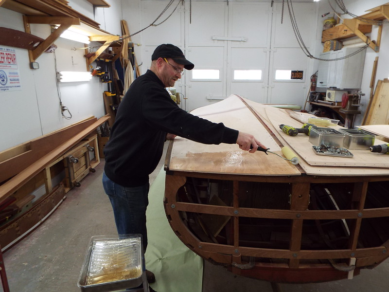 Applying epoxy to hull for the second bottom skin.
