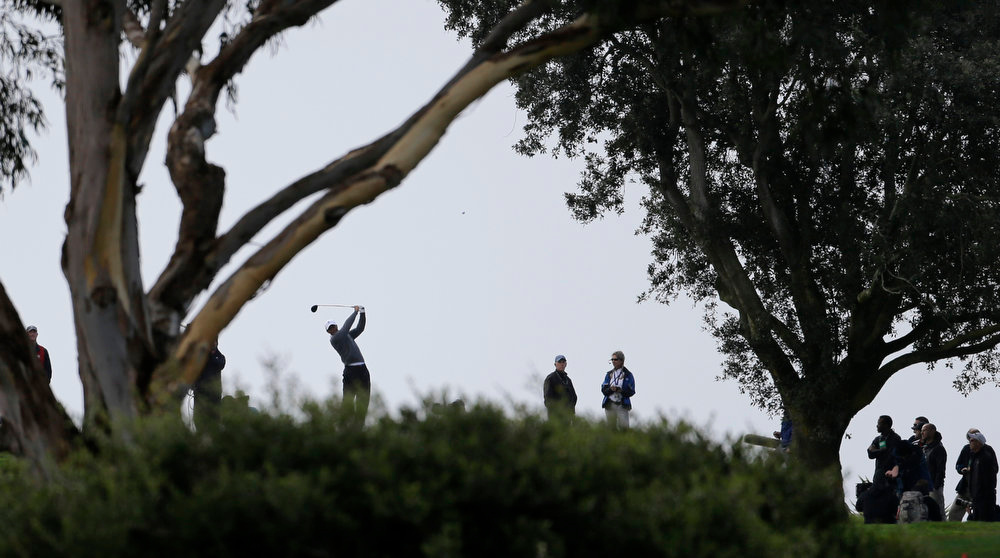 Description of . Tiger Woods drives from behind the trees on the south hole of the South Course at Torrey Pines during the third round of the Farmers Insurance Open golf PGA tournament Sunday, Jan. 27, 2013, in San Diego. (AP Photo/Lenny Ignelzi)