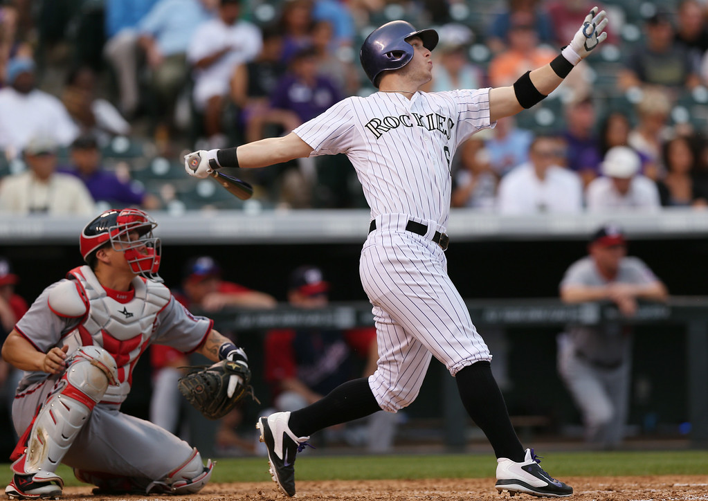 . Colorado Rockies\' Corey Dickerson, right, follows the flight of his double with Washington Nationals catcher Jose Lobaton in the fifth inning of a baseball game in Denver on Wednesday, July 23, 2014. (AP Photo)